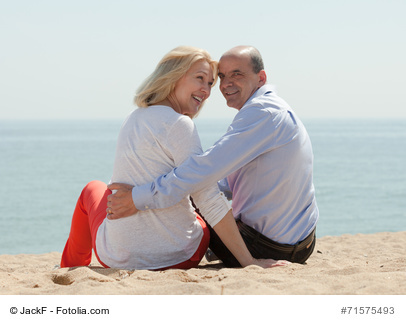 Smiling mature lovers sitting on beach at seashore