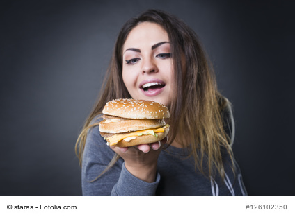 Happy beautiful young plus size model posing with hamburger on a gray studio background, xxl woman eating burger, fast food and unhealthy nutrition concept